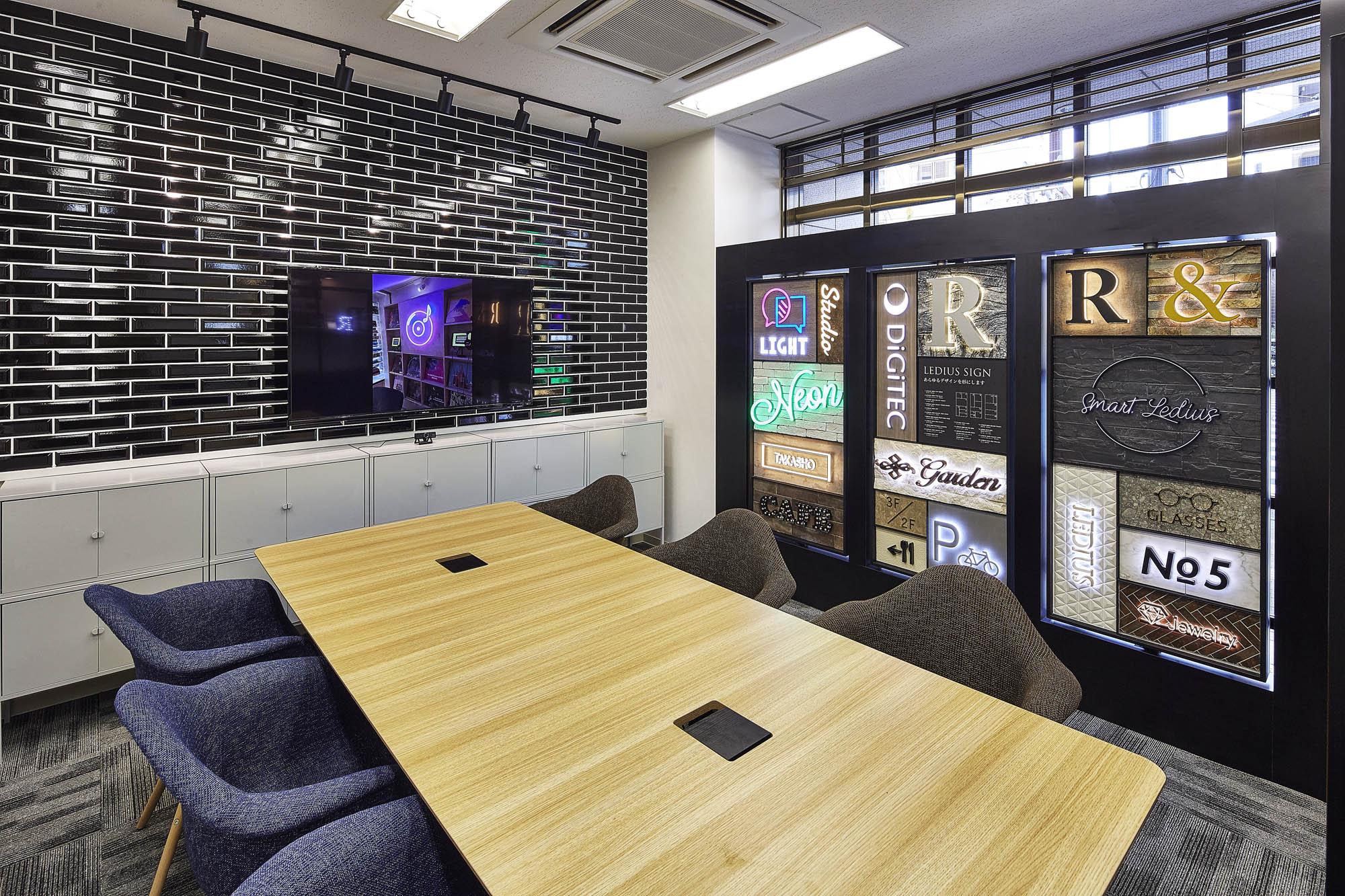 実際のLEDサインサンプルを見せながら相談・商談を行うオフィスの写真