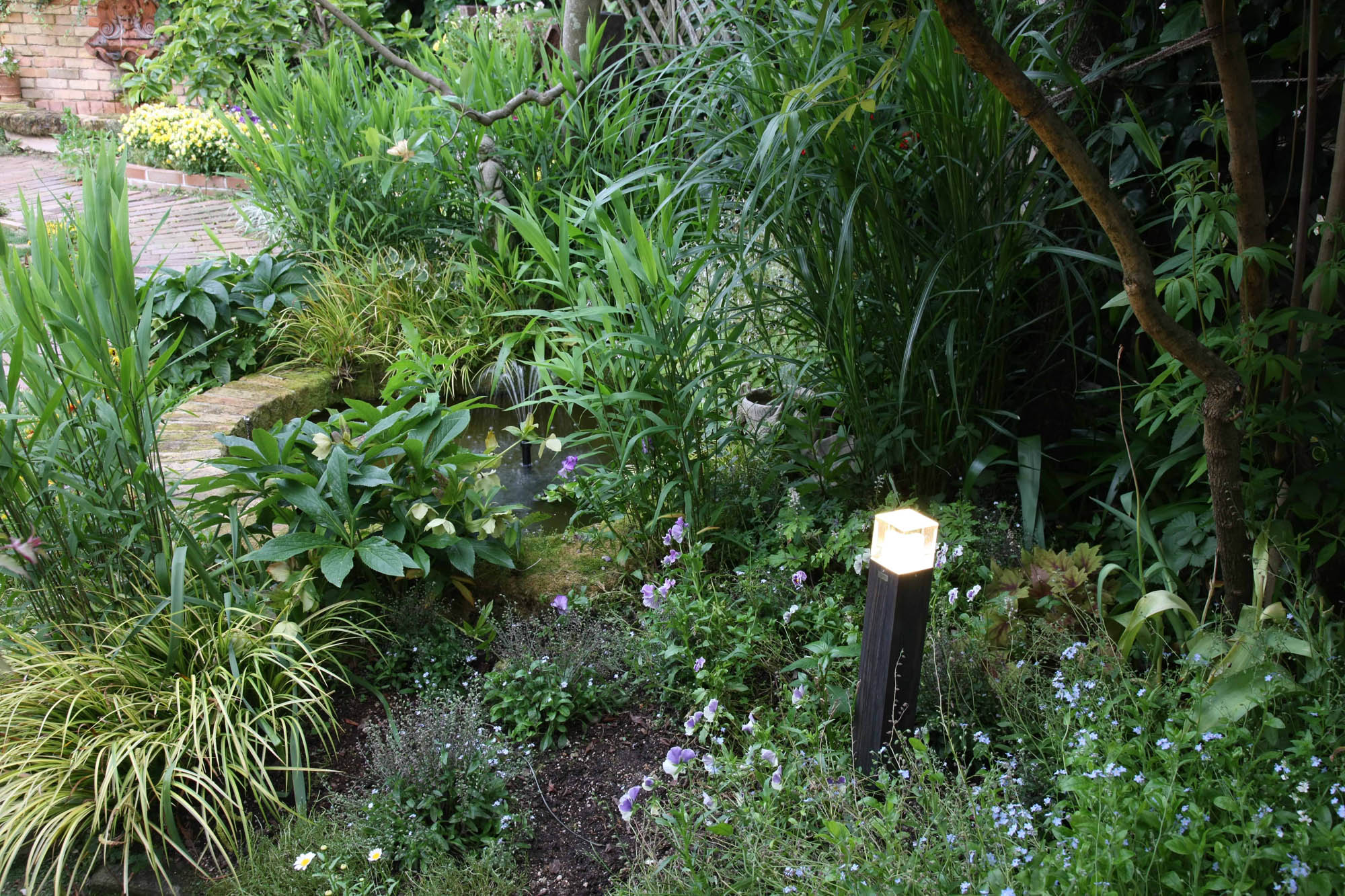 植栽の中に木目調のエバーアートポールライトを取り入れた例
