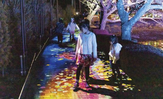 プロジェクションマッピングであるフラワーシャワーカーペットを歩く子供たちの写真