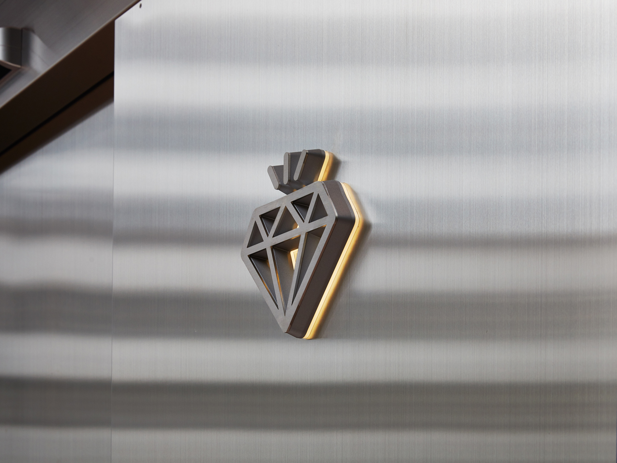 壁面のステンレスと塗装の金属感を合わせて光をアクセントにした例の写真